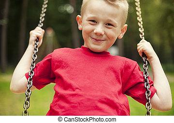 Close-up of little boy swinging