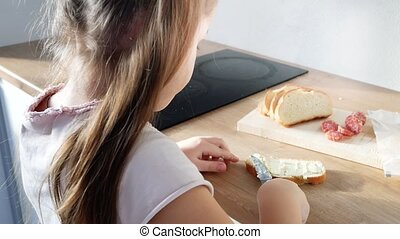 little child making sandwich with butter and sausage - Close...