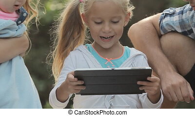 Close up of little curious girl with tablet sitting with her family