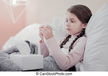 Close up of little sad girl with napkins - Flu. Close up of...