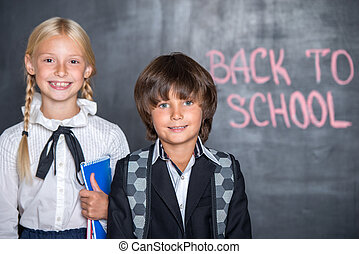 Close-up of little school boy and girl near blackboard
