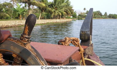 Close up of local steering boat through riverbank - Close up...