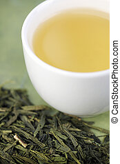 Close-up of loose green tea and cup - Close-up of loose...