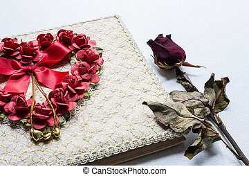 Close up of Love diary and Roses wilt on white canvas background