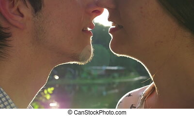 Close-up of loving couple kissing at sunset