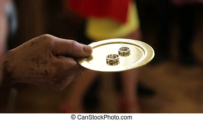 Close up of luxurious rings on gold plate in the church. Wedding ceremony