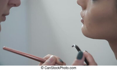Close up of make up for beautiful model, applying lipstick pencil