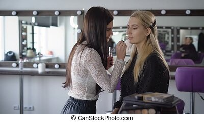 Close up of make-up process at stylish beauty shop. Young visagiste is contouring mouth line using special lip line on model's face. Brunette artist creating an image of model for future photography.