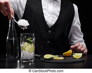 Close-up of making a refreshing shake process. Bartender adding crushed ice to a citrus cocktail on a black background.