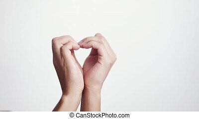 Close up of making heart from female hands on a white...