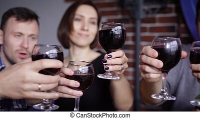 Close up of male and female hands clinking glasses with red wine to each other with happy faces in the background. Group of people celebrating party at the restaurant talking and smiling.