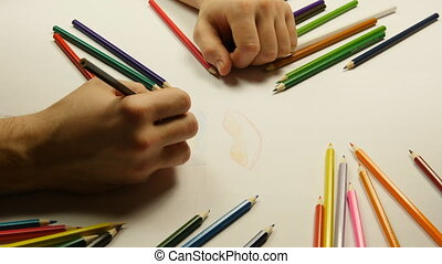 Close up of male and female hands taking colored pencils and drawing together
