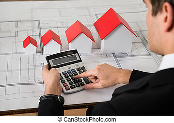 Architect Calculating In Front Of House Models On Blue Print