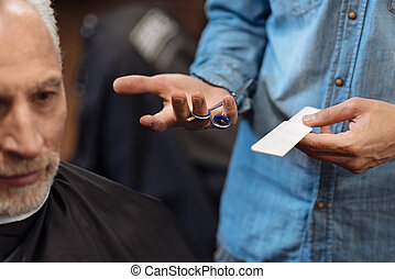 Close up of male barber holding scissors and comb