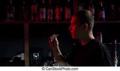 Close-up of male bartender blowing on coals in hookah bar.