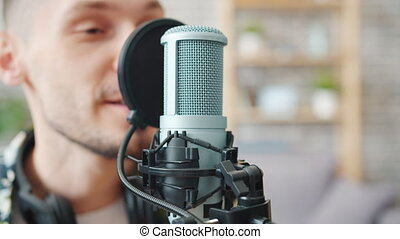 Close-up of male blogger talking in microphone recording...
