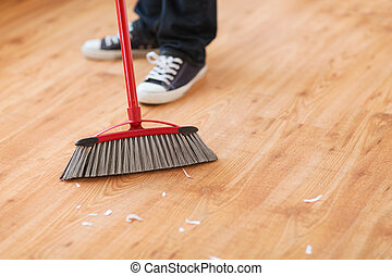 close up of male brooming wooden floor - cleaning and home...