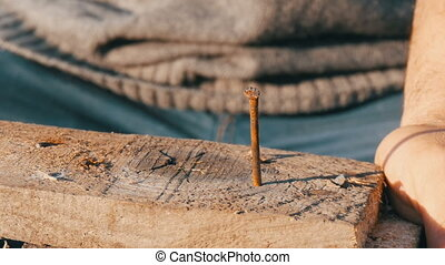 Close up of male carpenter hammers iron nail into a wooden...