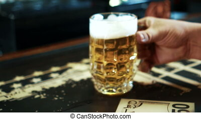 Close up of male client who is catching the beer mug by his hand in the bar, slow motion.