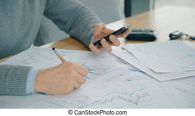 Close up of male financial analytic makes calcutaions on his smartphone and correcting data on paper.