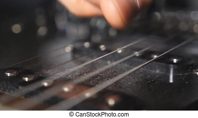 Close up of male fingers touching strings of a musical...