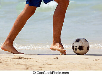 Close up of male foot playing football on sand