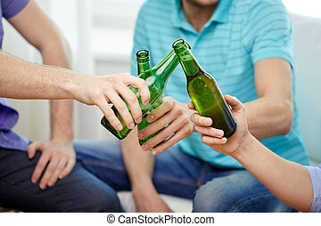 friendship, alcohol, people, celebration and holidays concept - close up of male friends drinking and clinking beer bottles at home