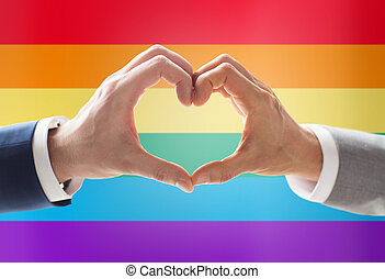 close up of male gay couple hands showing heart
