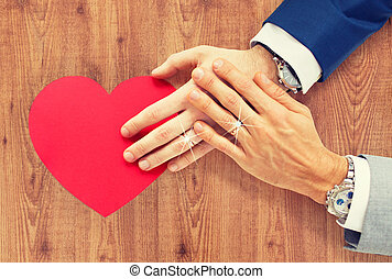 close up of male gay couple hands with red heart