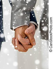 close up of male gay couple holding hands - people, ...