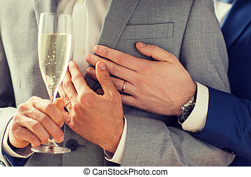 close up of male gay couple with champagne glass