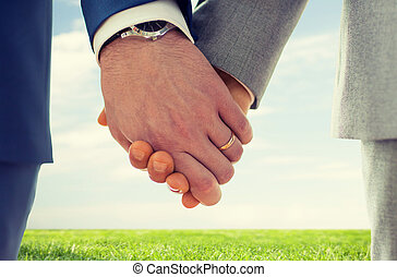 close up of male gay hands with wedding rings on - people, ...