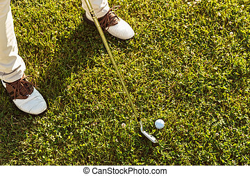 Close-up of male golfer teeing off
