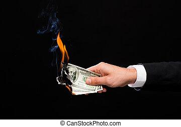close up of male hand holding burning dollar money