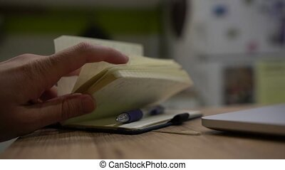 Close up of male hand opening notebook and writing with pen