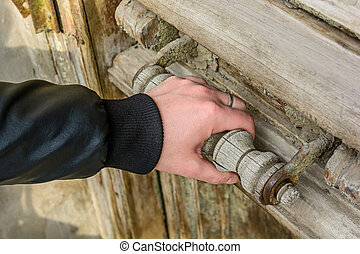 Close up of male hand opening old wooden door