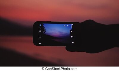 Close up of male hand taking a picture of beautiful sunset on the beach with mobile phone. Slow motion. 1920x1080