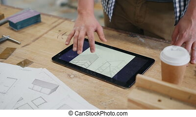 Close-up of male hand touching tablet screen in wood workshop indoors