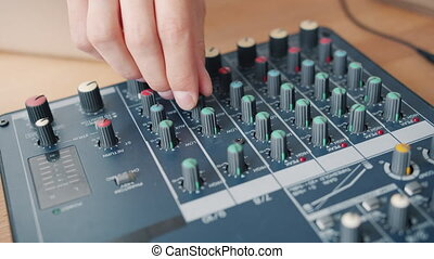 Close-up of male hand working with sound mixer indoors recording audio podcast in studio, equipment is placed on table. People and modern technology concept.