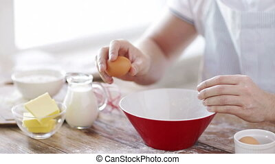 close up of male hands cracking an eggl - cooking and home...