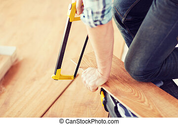 close up of male hands cutting parquet floor board - repair,...