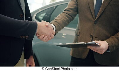 Close up of male hands getting car keys after successful deal with sales manager and shaking hands in dealership. Buying and selling autos, businessmen and handshake concept.