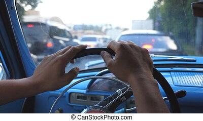 Close up of male hands holding on a steering wheel of old retro car and nervously tapping fingers. Unrecognizable man standing in traffic jam at downtown. POV Slow motion