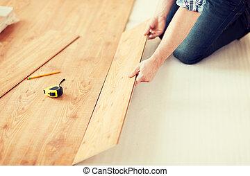 close up of male hands intalling wood flooring - repair,...