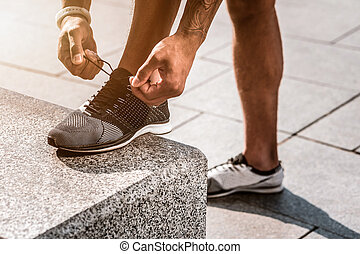 Close up of male hands lacing the shoes