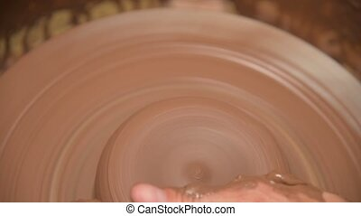 Close-up of male hands making a clay bowl on a potter's ...