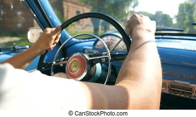 Close up of male hands on the steering wheel of a retro car. Unrecognizable man drives a vintage auto in the city street on sunny summer day. Young guy inside his old blue automobile. Slow motion