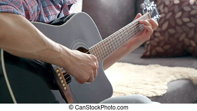 Close-up of male hands playing acoustic guitar at home