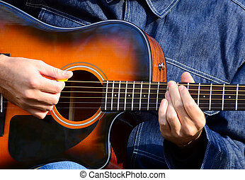 Close up of male hands playing guitar