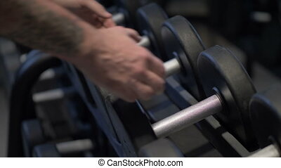 Close-up of male hands taking the dumbbell
